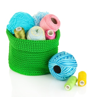 Fios coloridos para tricô em cesta verde isolada no branco
