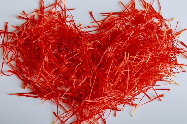 Fios de açafrão em forma de coração em um fundo branco. preparação de fios de açafrão para secagem antes do uso em culinária, cosmetologia ou medicina.