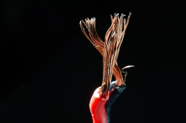 Fios de cobre descobertos em preto e vermelho em um fundo escuro. macro.