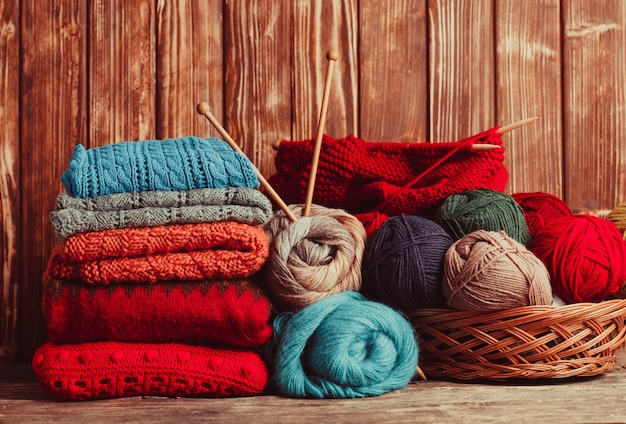 Fios de cor, agulhas de tricô e roupas na mesa de madeira