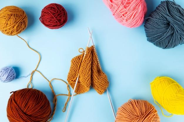 Fios de cor para tricô, fundo azul. projeto de tricô em andamento. vista do topo