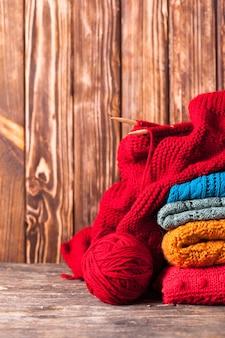 Fios de cores, agulhas de tricô e roupas com espaço de cópia