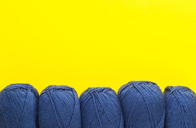 Fios de tricô da clássica cor jeans azul sobre amarelo
