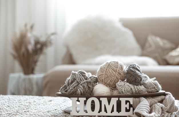 Fios de tricô na mesa e letras de madeira para casa