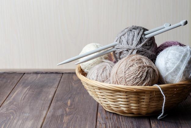 Fios e agulhas de tricô em uma cesta de vime redonda