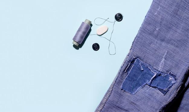 Fios e botões em um espaço azul ao lado do jeans. copie o espaço.