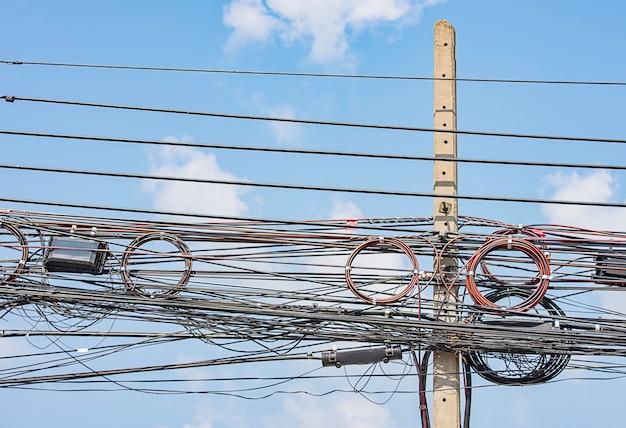 Fios e cabos elétricos que penduram em uma coluna concreta e no céu azul brilhante.