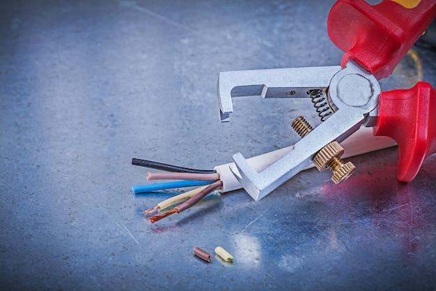 Fios elétricos de strippers de isolação na mesa metálica riscada, conceito de eletricidade