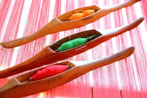 Fios na lançadeira de madeira em fios vermelhos, fundo abstrato do teste padrão.