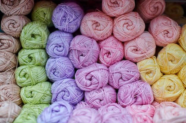 Fios ou bolas de lã nas prateleiras da loja para tricô e bordado