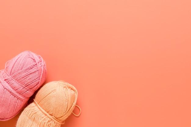 Fios para tricô em fundo laranja