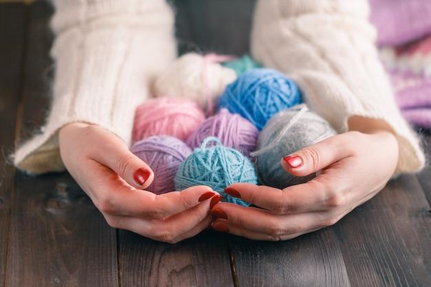 Fios para tricotar nas mãos das mulheres