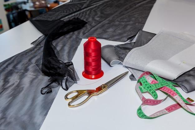 Fios, tesouras e tecidos colocados na mesa de madeira branca.