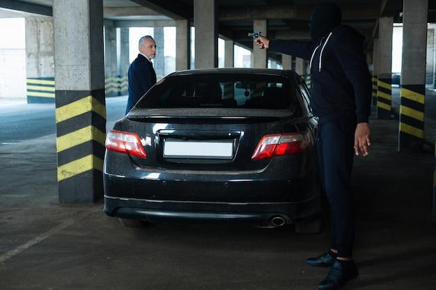Fique aqui. homem de negócios bonito, bonito, parado perto de seu carro e pretendendo entrar nele enquanto se torna vítima de um crime