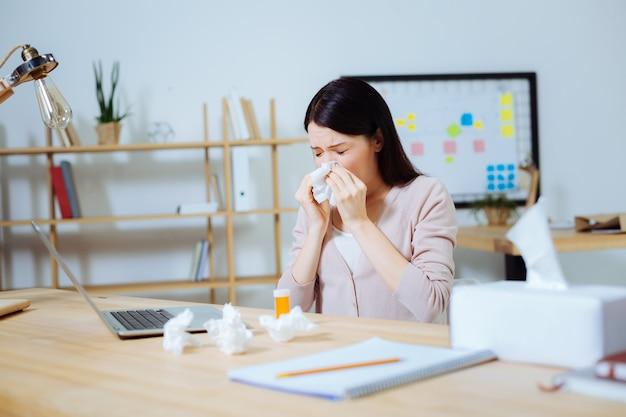 Fique bem logo. mulher doente, mantendo os olhos fechados e cobrindo o nariz enquanto espirra