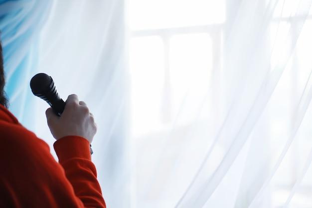 Fique com um microfone. homem segura as mãos de um microfone em um tripé. performance do artista com microfone. cena com microfone.