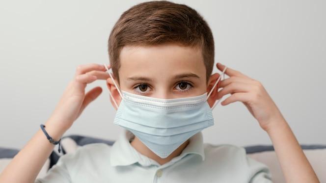 Fique dentro de casa criança usando máscara médica
