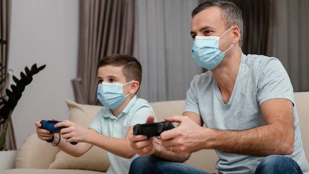Fique dentro de casa, homem e criança jogando videogame
