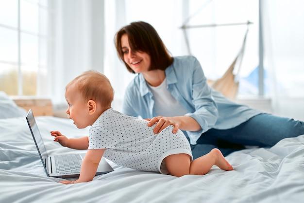 Fique em casa, a mãe trabalha remotamente no laptop, cuidando do bebê. uma jovem mãe em licença maternidade tenta trabalhar na cama com um filho pequeno. feche acima, copie o espaço, o plano de fundo.