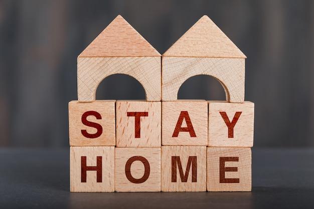 Fique em casa conceito com blocos de madeira, cinza em casa de madeira.