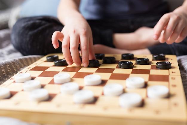 Fique em casa conceito de quarentena. jovem garoto mãos jogando jogo de mesa de damas na cama. jogo de tabuleiro e conceito de lazer de crianças. tempo para a família.