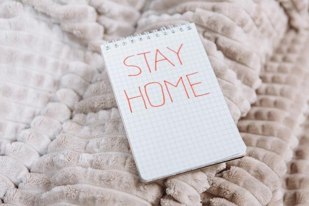 Fique em casa escrevendo em um bloco de notas, epidemia da doença coronavírus