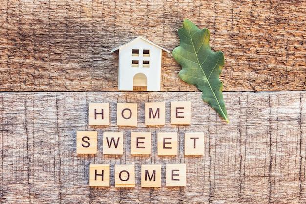 Fique em casa, fique seguro. casa de brinquedo em miniatura com inscrição casa palavra doce letras casa na parede de madeira. consciência social de distanciamento.