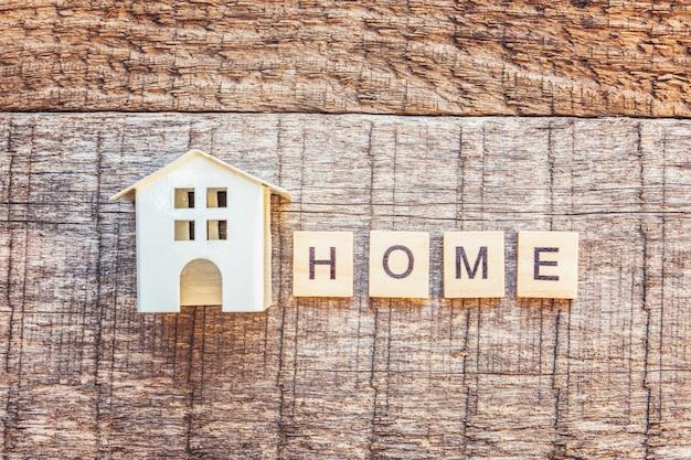 Fique em casa, fique seguro. casa de brinquedo em miniatura com inscrição letras casa palavra na parede de madeira. consciência social de distanciamento.