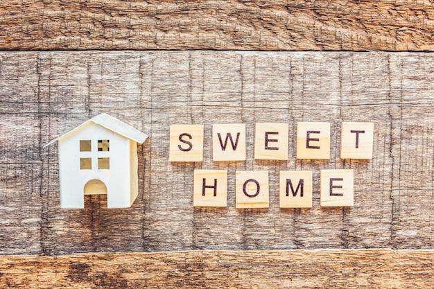 Fique em casa, fique seguro. casa de brinquedo em miniatura com inscrição palavra doce letras casa na parede de madeira. consciência social de distanciamento. s