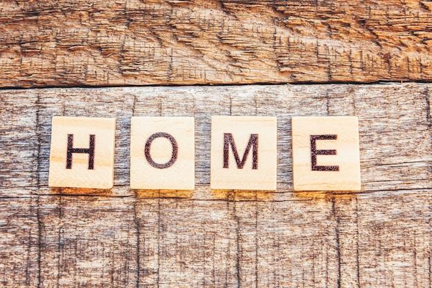 Fique em casa, fique seguro. inscrição em casa letras palavra na parede de madeira. consciência social de distanciamento.
