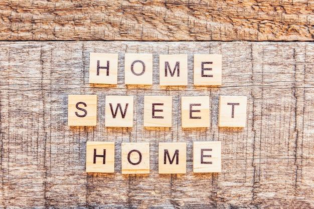 Fique em casa, fique seguro. palavra de letras casa doce casa inscrição na parede de madeira. consciência social de distanciamento.