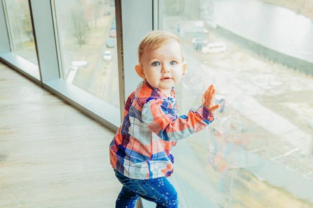 Fique em casa, fique seguro. pequeno doce infantil bebê menina bonitinha ficar perto da grande janela na sala de estar de luz brilhante em casa dentro de casa. conceito de ternura de maternidade familiar de infância.