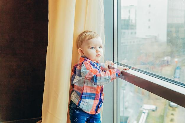 Fique em casa, fique seguro. pequeno doce infantil bebê menina sentada perto da grande janela na sala de estar de luz brilhante em casa dentro de casa. conceito de ternura de maternidade familiar de infância.
