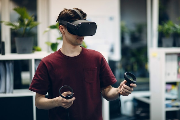 Fique em casa. jovem em realidade virtual auricular, óculos vr com joystick jogando.