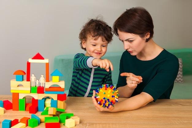Fique em casa. mãe e bebê brincam em casa. explique à criança o que é o vírus de uma forma lúdica.
