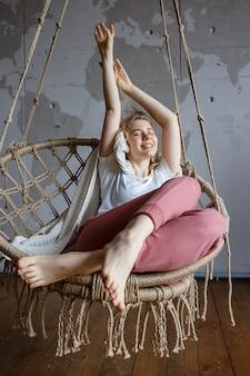 Fique em casa: passando tempo com alegria. linda garota no balanço no quarto loft