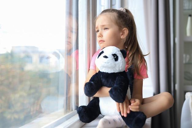 Fique em casa, quarentena, prevenção da pandemia de coronavírus. criança triste com máscara médica protetora e seu urso panda sentado no parapeito da janela, olhando pela janela.