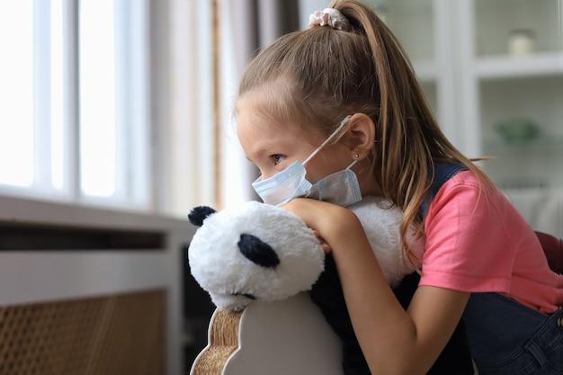 Fique em casa, quarentena, prevenção da pandemia de coronavírus. criança triste com máscara médica protetora e seu urso panda sentar no cavalo de balanço, olhando pela janela.