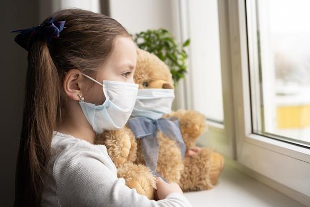 Fique em casa, quarentena, prevenção da pandemia de coronavírus. criança triste e seu ursinho de pelúcia com máscaras médicas de proteção sentados no parapeito da janela e olhando pela janela