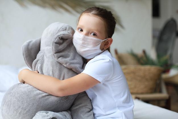Fique em casa, quarentena, prevenção da pandemia de coronavírus. criança triste na máscara médica protetora e seu elefante, ambos na máscara médica protetora, sentam-se na cama.