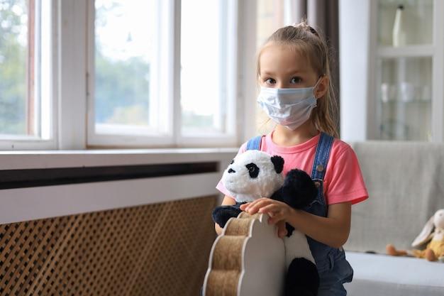 Fique em casa, quarentena, prevenção da pandemia de coronavírus. criança triste na máscara médica protetora e seu urso panda sentar no cavalo de balanço.