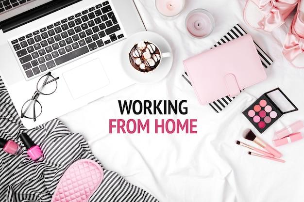 Fique em casa, quarentena. trabalhando em casa. espaço de trabalho com laptop e acessório de mulher na cama. disposição plana, vista de cima