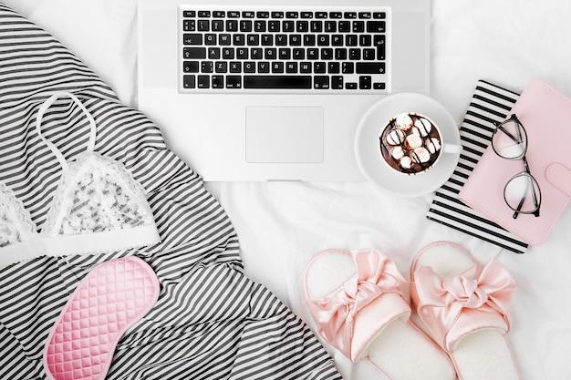 Fique em casa, quarentena. trabalhando em casa. espaço de trabalho feminino com laptop e acessório feminino na cama. disposição plana, vista de cima