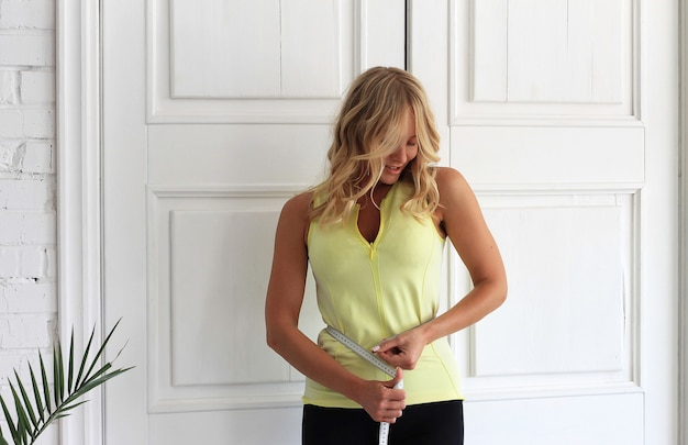 Fique em forma. jovem mulher com corpo atlético mede sua cintura com um tipo de medida