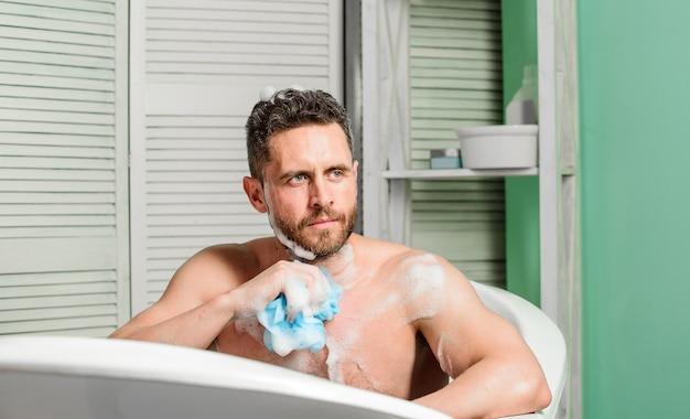 Fique limpo e fresco. cuidado pessoal. homem sexy no banheiro. higiene e saúde. banho da manhã. machão lavando no banho. homem lava corpo musculoso com esponja de espuma. meu relaxamento.