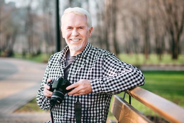 Fique no momento. homem maduro vigoroso usando câmera e sentado no parque