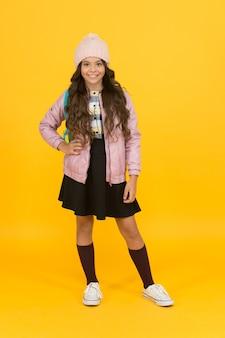 Fique quente, fique frio. menina de volta à escola com look de outono. criança feliz usar gorro com aparência de escola de tendência. look vogue de uma pequena modelo. moda infantil para o outono e a escola.