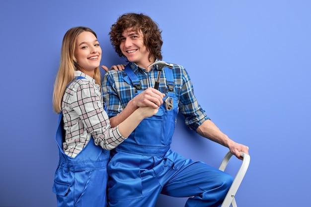 Firendly, homem e mulher uniformizados, trabalhando juntos, usando ferramentas domésticas