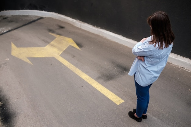 Firl em pé perto de duas setas impressas na estrada do grunge, tomando decisões