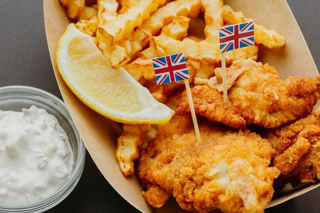 Fish and chips com molho e bandeiras da grã-bretanha